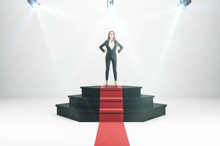 Happy businesswoman on illuminated pedestal. Winner and success concept. Reklamní fotografie