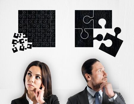 Attractive young european businessman and woman with puzzles overhead on light background. Teamwork and strategy concept Reklamní fotografie