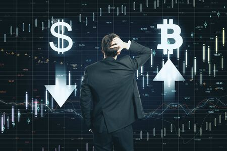 Dollar and bitcoin concept. Back view of thoughtful young businessman making decision on abstract forex chart grid background