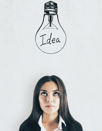 Portrait of attractive young european businesswoman with lightbulb sketch on light background. Idea and think concept