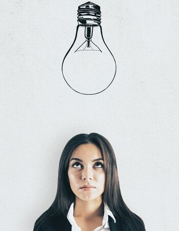 Portrait of attractive young european businesswoman with lamp sketch on light background. Idea and think concept