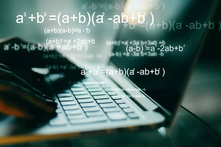 Programming and algorithm concept. Close up of hands using blurry laptop with mathematical formulas. Double exposure