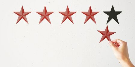 Hand with star rating on subtle background. Evaluation and assessment concept