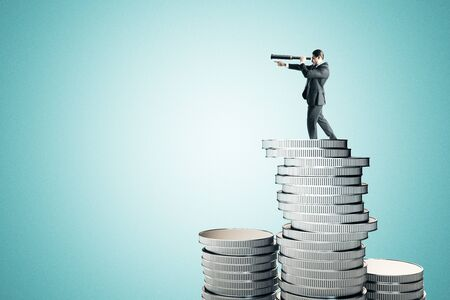 Side view of young businessman with telescope standing on pile of silver coins. Blue background. Vision and money concept.
