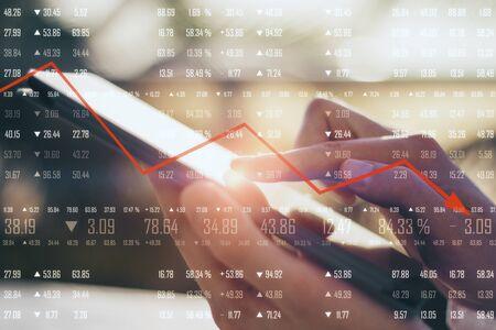 Cerca de la mano con tableta con dígitos financieros y flecha roja hacia abajo sobre fondo borroso. Concepto de declive económico. Multiexposición