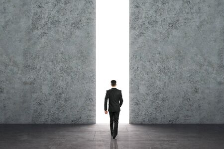 Businessman walking towards bright opening in concrete wall. Opportunity and success concept.