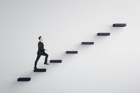 Side view of young businessman climbing stairs to success on concrete wall background. Leadership and development concept Stockfoto