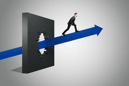 Businessman on arrow breaking through wall on grey background. Breakthrough and success concept.