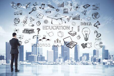 Hintere Ansicht des durchdachten jungen Geschäftsmannes, der Stadt mit Geschäftsskizze betrachtet. Idee und Bildungskonzept. Doppelbelichtung