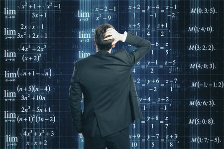 Back view of stressed young businessman looking at mathematical formulas on dark background. Programming, science, knowledge and complex algorithm concept Archivio Fotografico