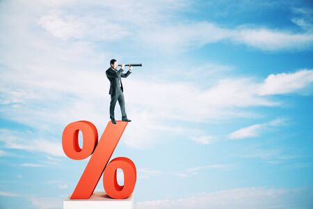 Side view of young businessman standing on red percent sign and looking into the distance on blue sky with clouds background. Interest rate, investment and loan concept