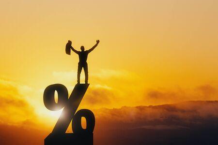 Vista frontale dell'uomo d'affari felice in piedi sul segno di percentuale retroilluminato su sfondo bellissimo tramonto. Tasso di interesse, investimento e concetto di prestito Archivio Fotografico