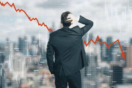 Vista posterior del joven empresario estresado mirando la flecha roja hacia abajo sobre fondo borroso de la ciudad. Disminución, estadísticas y concepto de economía. Multiexposición