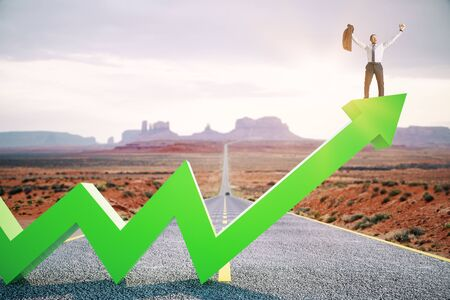 Happy businessman standing on upward green arrow on abstract road and desert background. Growth, development, success and increase concept.