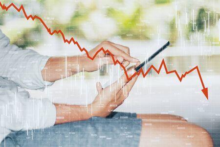 Close-up en zijaanzicht van handen met smartphone met neerwaartse rode grafiekpijl. Daling, internet en marktconcept. Dubbele blootstelling Stockfoto