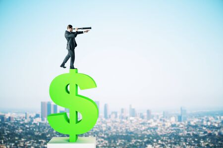 Side view of young businessman silhouette standing on dollar sign and looking into the distance on blurry city  background. Research and income concept 版權商用圖片