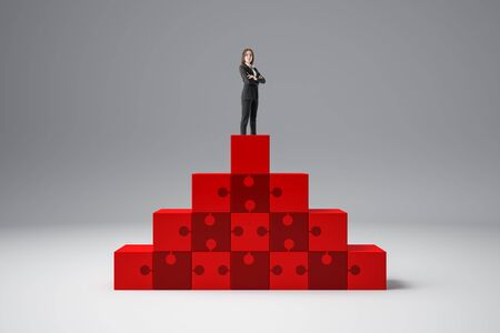 Businesswoman standing on abstract red puzzle pedestal on grey background. Leadership and success concept.