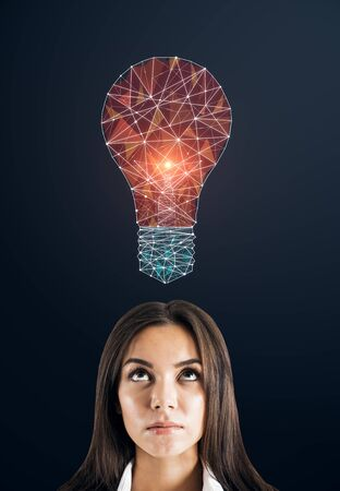 Thoughtful young businesswoman portrait with creative polygonal light bulb on dark background. Innovation, technology and solution concept
