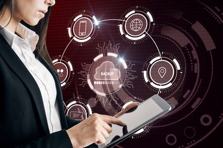Attractive businesswoman using tablet with creative glowing cloud computing interface on dark background. Backup and storage concept. Double exposure