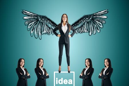 Happy young businesswoman with drawn wings standing on pedestal on subtle blue background with other businesspeople. Idea and confidence concept Archivio Fotografico - 127600303