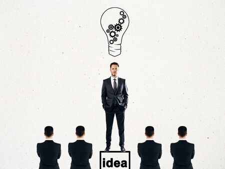 Businessman with drawn light bulbs standing on pedestal on subtle white background with other businesspeople. Idea and leadership concept