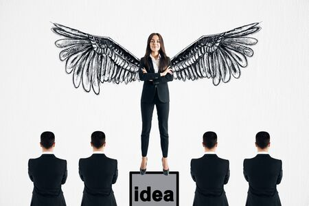 Happy young businesswoman with drawn wings standing on pedestal on subtle white background with other businesspeople. Idea and leadership concept Archivio Fotografico - 127352250