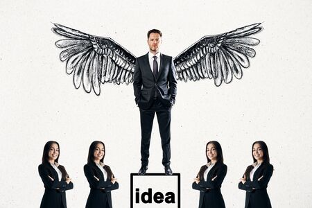 Businessman with wings standing on pedestal on subtle white background with other businesspeople. Idea and hero concept