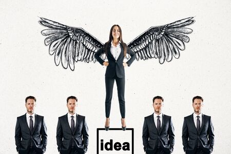 Happy young businesswoman with drawn wings standing on pedestal on subtle white background with other businesspeople. Idea and boss concept Zdjęcie Seryjne