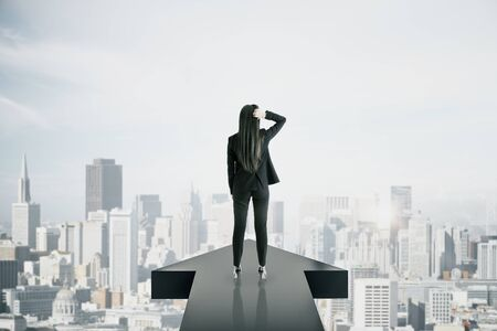 Back view of young businesswoman standing on arrow on New York city background. Growth and leadership concept