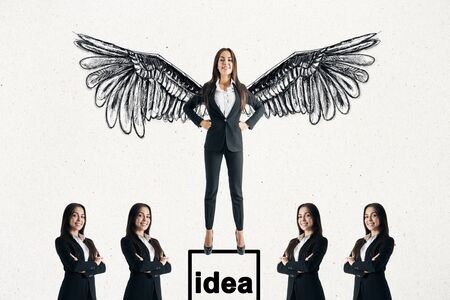 Happy young businesswoman with drawn wings standing on pedestal on subtle white background with other businesspeople. Idea and success concept