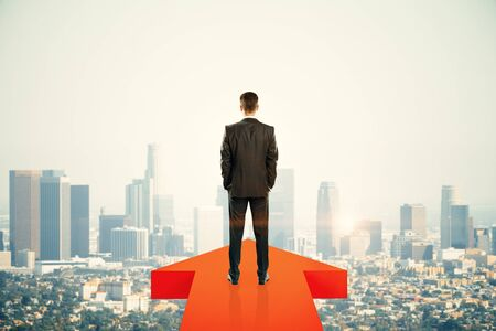 Back view of young businessman standing on red arrow on New York city background. Growth and success concept Stok Fotoğraf