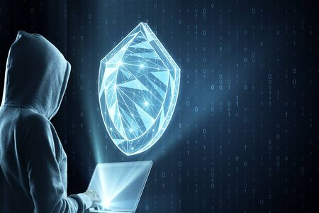 Hacker using laptop with creative glowing blue polygonal antivirus shield on dark binary code background. Safety and protection concept. Multiexposure