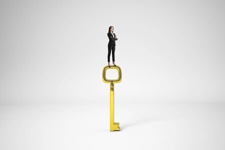 Businesswoman standing on golden key and looking into the distance on white background. Access and vision concept