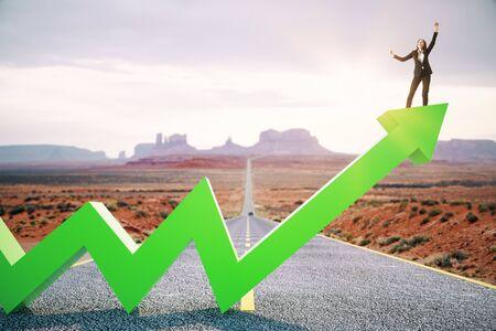 Glückliche Geschäftsfrau, die auf grünem Pfeil aufwärts auf abstraktem Straßen- und Wüstenhintergrund steht. Wachstum, Entwicklung, Erfolg und Steigerungskonzept.