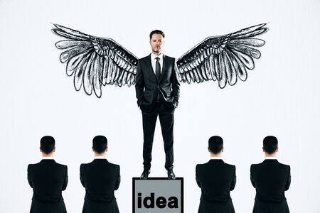 Businessman with wings standing on pedestal on subtle white background with other businesspeople. Idea and leadership concept Archivio Fotografico - 127355168
