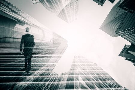 Back view of young businessman walking on abstract black-and-white city background. Success and future concept. Multiexposure Stock Photo