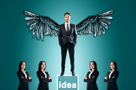 Businessman with wings standing on pedestal on subtle blue background with other businesspeople. Idea and leadership concept