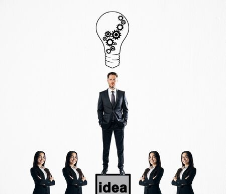 Businessman with drawn light bulbs standing on pedestal on subtle white background with other businesspeople. Idea and success concept Banco de Imagens