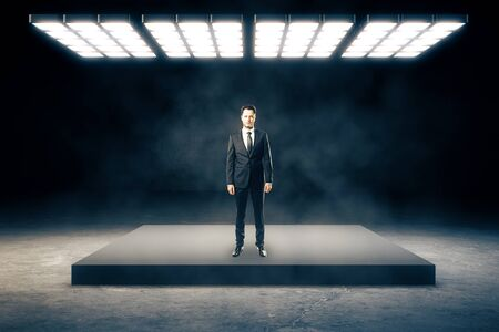 Man standing in abstract smoky interior with bright ceiling lamp. Success and leadership concept. Reklamní fotografie