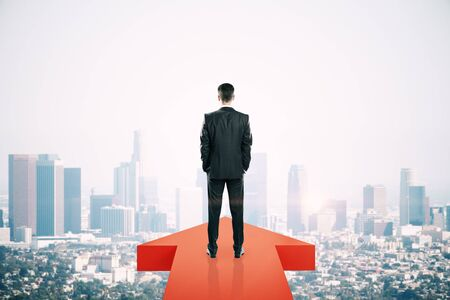 Back view of young businessman standing on red arrow on New York city background. Growth and forward concept