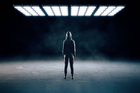 Back view of person in hoodie standing in abstract smoky interior with bright ceiling lamp. Research concept.