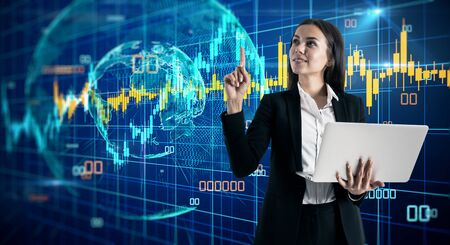 Attractive happy young european businesswoman with laptop using abstract digital forex interface with globe. Global business and stock concept. Multiexposure