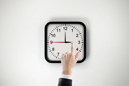 Businessman hand pointing at clock dial on white wall background. Time management and deadline concept