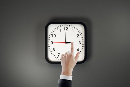 Businessman hand pointing at clock dial on grey wall background. Time management and deadline concept
