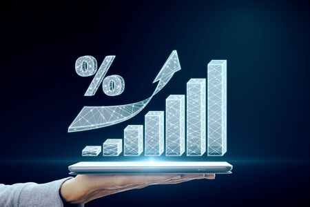 Hand holding tablet with abstract polygonal business chart and interest on dark background. Invest and stock concept. Archivio Fotografico - 127974652