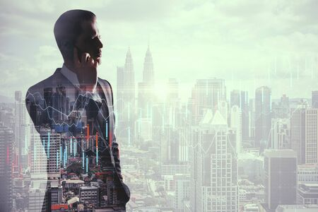 Businessman talking on the phone on blurry city background with forex chart. Finance and communication concept. Multiexposure