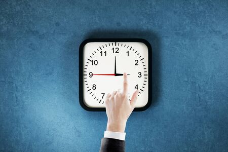 Businessman hand pointing at clock dial on blue wall background. Time management and deadline concept Stock Photo