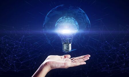 Hand holding glowing polygonal light bulb with globe on dark blue background. Worldwide innovation and interface concept
