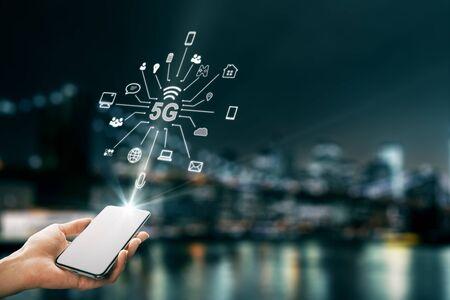 Main à l'aide d'un smartphone avec une interface 5G abstraite avec des icônes informatiques sur fond de ville de nuit floue. Vitesse Internet et concept d'IA. Double exposition