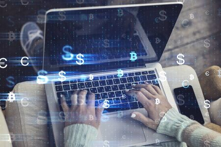 Female hands using laptop placed on lap with cup glowing money signs. Cryptocurrency and future concept. Double exposure